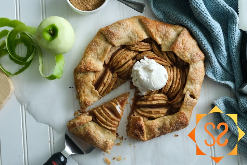An apple galette with a slice being pulled away, topped with vegan ice cream; a peeled apple to the left, and a ramekin of brown sugar above.