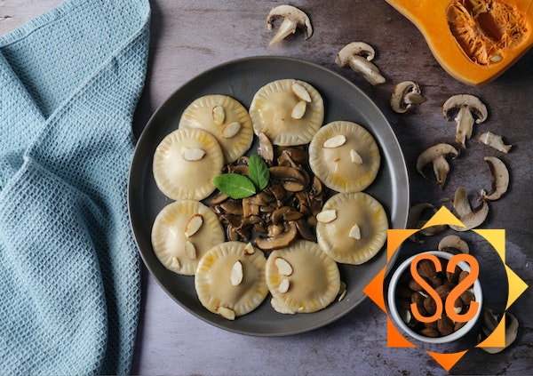Vegan butternut squash ravioli on a plate with mushrooms, squash, and almonds nearby