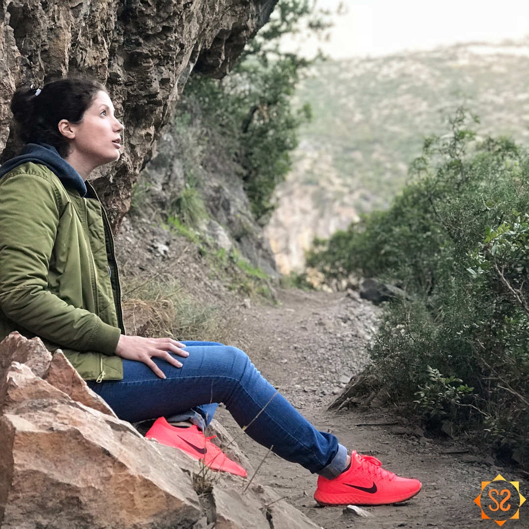Steph sitting on a rock, taking a break from hiking in Talassemtane National Park