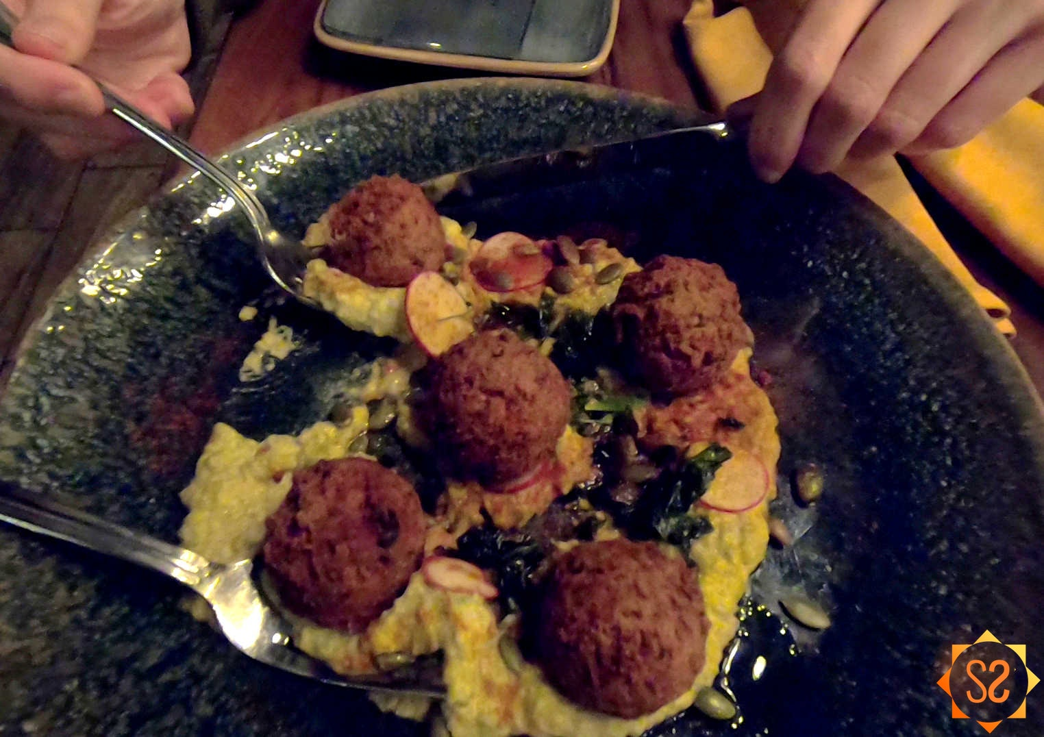 Falls Family Falafel on a plate, one piece being scooped out by a fork