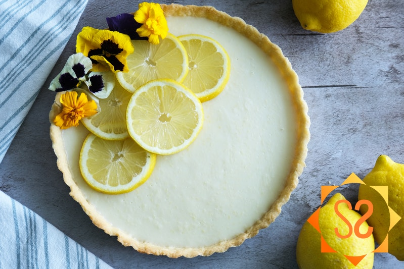 A top-down view of a lemon tart topped with lemon slices and flowers; a kitchen towel and lemons to the sides.