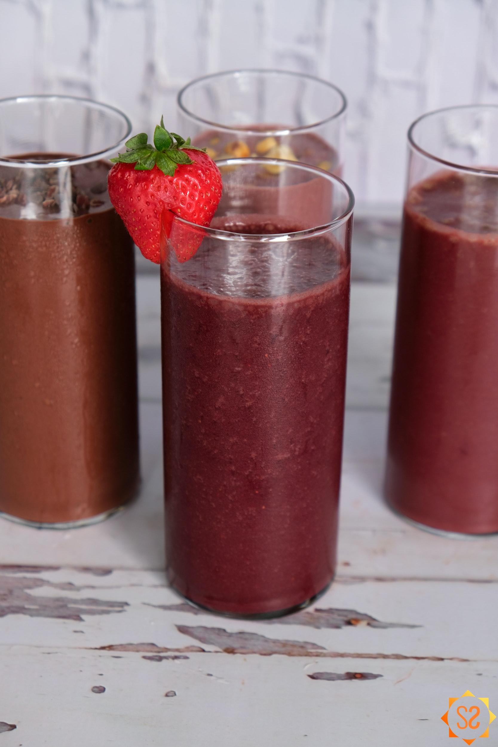 Strawberry açaí smoothie surrounded by three other açaí smoothies
