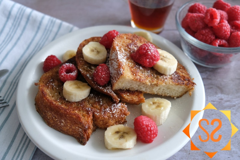 vegan French toast on a plate with bananas and raspberries