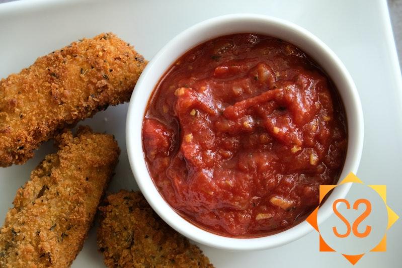 spicy marinara sauce in ramekin with mozzarella sticks on side