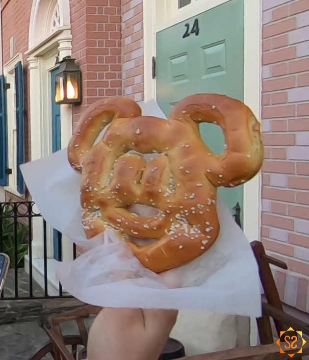 Mickey Pretzel in a hand in front of a Disney townhouse facade.