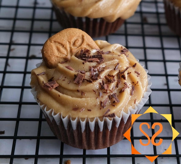 A closeup of a chocolate cupcake with cookie butter frosting, topped with shaved chocolate and a speculoos cookie